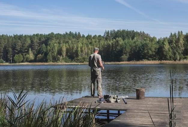 Рыбак на деревянном причале ловит рыбу на катушку летом