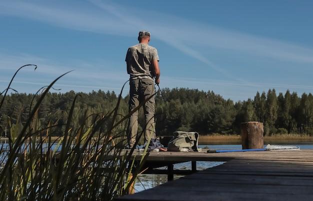 Рыбак на деревянном пирсе ловит рыбу на катушке, стоящей летом у озера