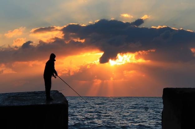 A fisherman on the rock against dawn sky