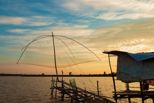 Fisherman's fishing tools in the lake at sunset sky .