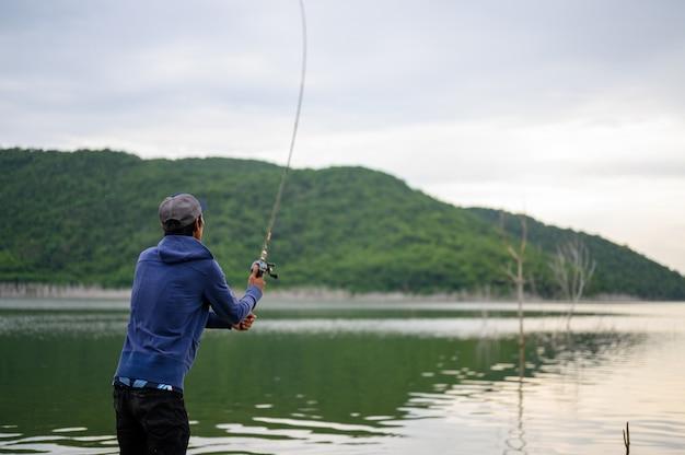 A fisherman's man is fishing at a natural lake