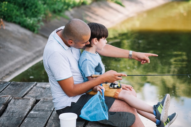 Fisherman showing something to his son while fishing on lake