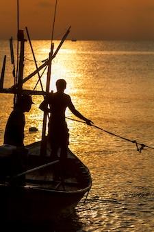 해돋이에 바다에서 어 부 실루엣