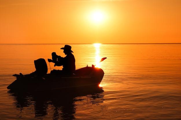 朝の陽光でボートに乗って漁師のシルエット