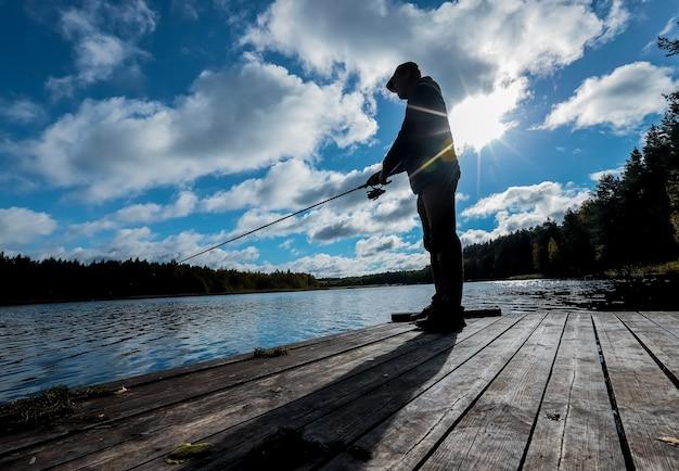 Силуэт рыбака, стоящего на деревянном пирсе, ловит рыбу на катушке с солнцем, сияющим за его спиной