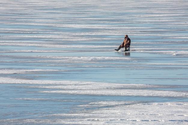フィンランド湾の氷の穴のそばに座っている漁師。
