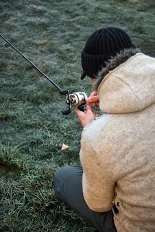 Рыбак сидит на земле и распутывает леску.