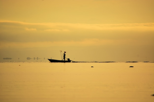 Fisherman standing on boat on sea