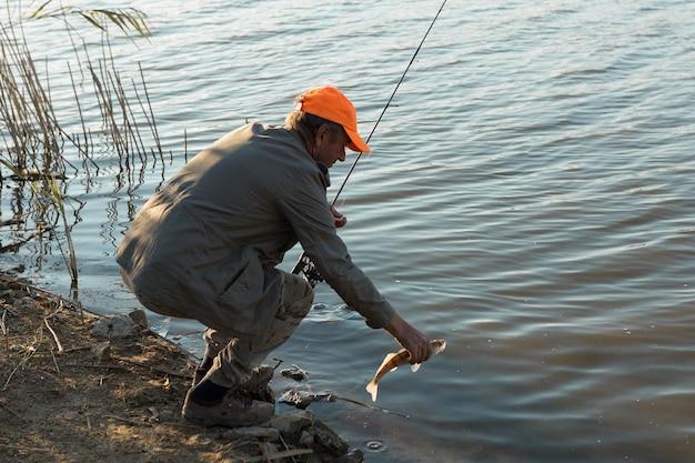Рыбак стоит на берегу реки и пытается поймать рыбу. спорт, отдых, образ жизни.