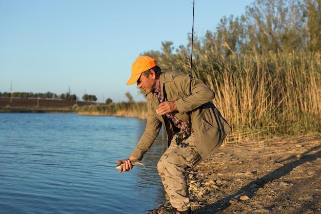 강변에 서서 물고기를 잡으려고 하는 어부. 스포츠, 레크리에이션, 라이프 스타일.