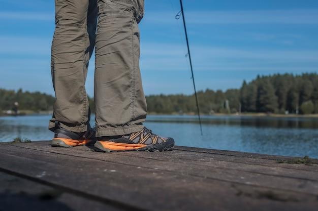 Рыбак, стоящий на деревянной пристани во время рыбалки летом