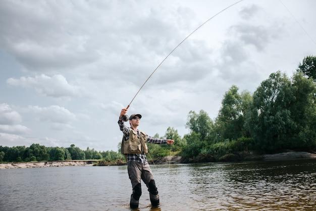漁師は片手でフライロッドを持ち、もう片方でスプーンの一部を持ち、浅く立っています。男は見上げています。彼は落ち着いて集中しています。
