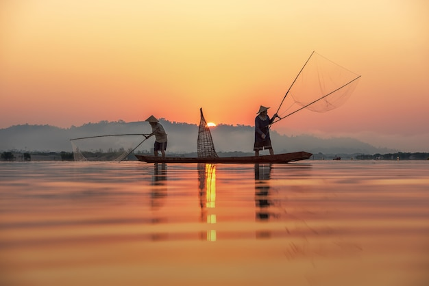 Fisherman on sunrise background at thailand countryside