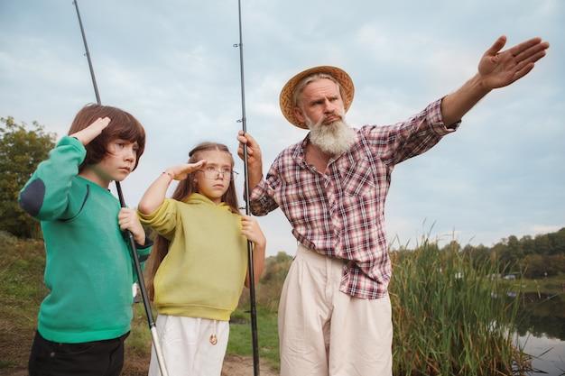 Рыбак учит своих внуков рыбалке на озере