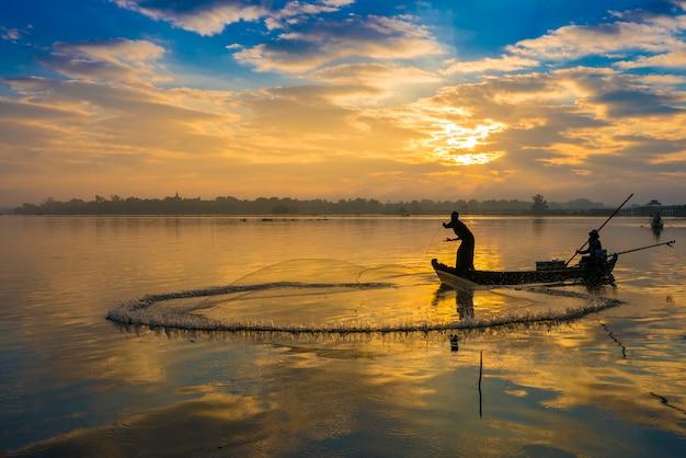 漁師は早朝にu bein橋の近く、日の出、ミャンマーのアマラプラ近くのタンタマン湖でネットを投げます。