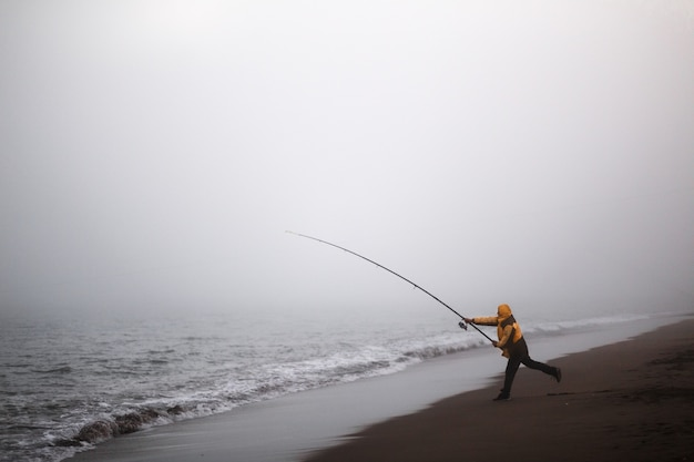 Fisherman throwing the rod on a beach with fog