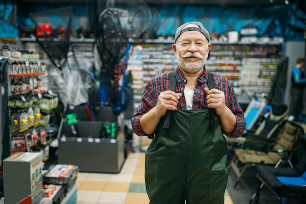 Рыбак примеряет резиновый комбинезон в рыболовном магазине, крючки и фенечки