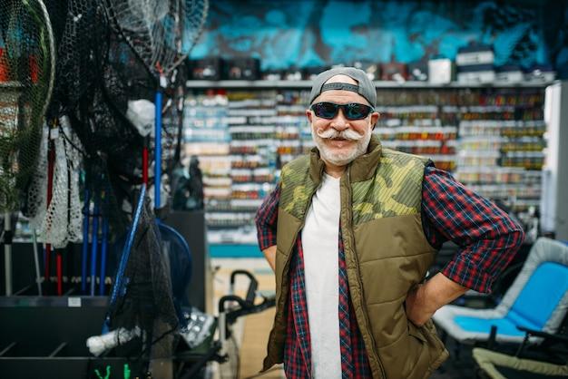 Рыбак примеряет солнцезащитные очки в рыболовном магазине.