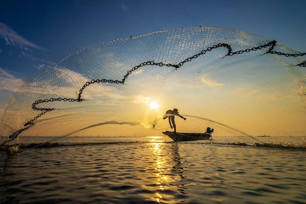 어부는 그물을 사용하여 바다에서 물고기를 잡습니다.