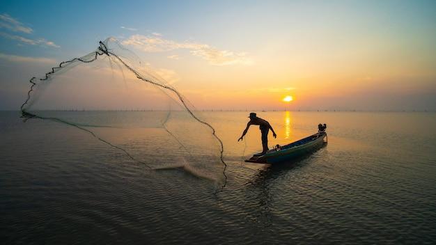Рыбак использует чистую добычу рыбы в море