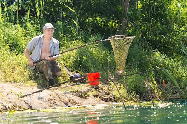 Fisherman using a net to land a fish