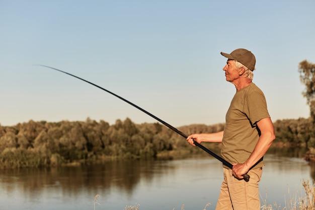 川でロッドフライフィッシングを使用する漁師、湖の土手に集中して顔を合わせ、魚を捕る、カジュアルな服を着ている漁師は、屋外で時間を過ごします。