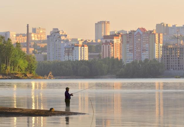 夜明けに水にひざまずく釣り竿を持つ漁師