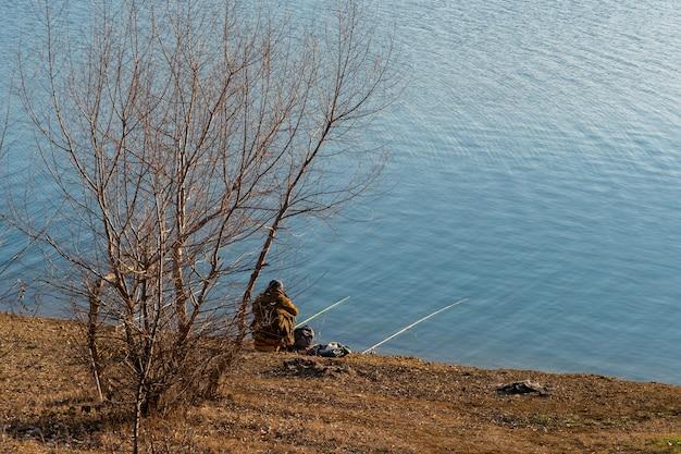 岸に座っている釣り竿を持つ漁師