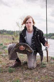 装備を持つ漁師は大きな魚を持っています。 asp。男は回転を続け、川の背景に座っています