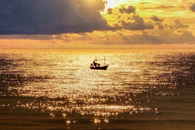 Fisherman with fishing boat sailing on golden sea in morning