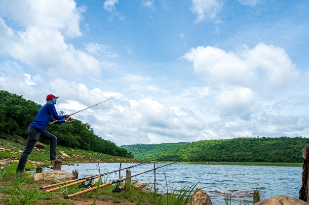 Fisherman with fishing rod on reservoir
