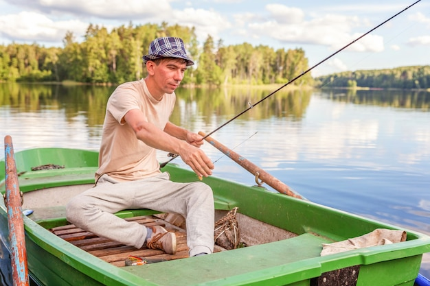 Fisherman with fishing rods is fishing in a wooden boat on lake or river