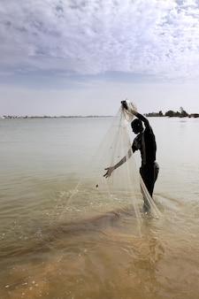 Pescatore con rete sul fiume
