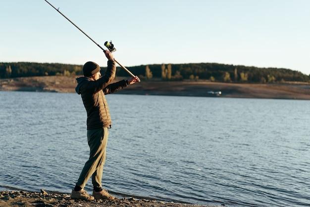 Рыбак с удочкой на озере
