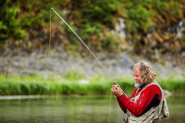 그의 손에 막대와 방수 천을 가진 어부는 강에서 플라이 낚시를 하고 있습니다.