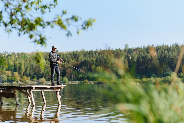 Рыбак с удочкой, спиннингом на берегу реки