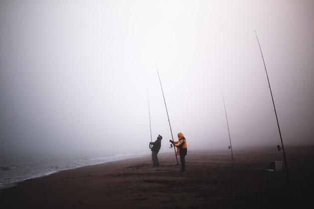 Fishermen on a beach with fog
