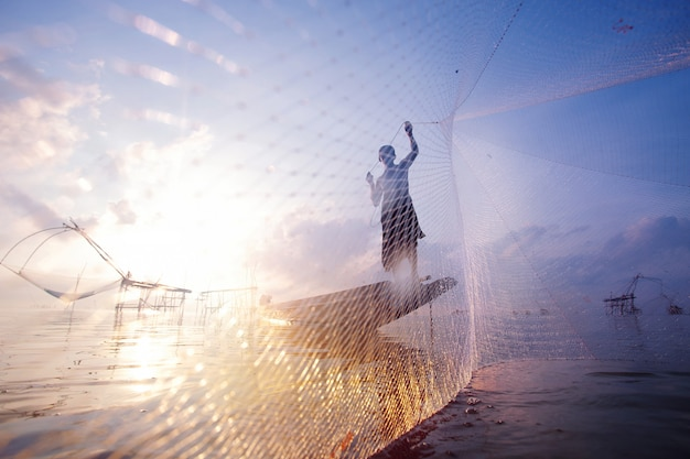 Fishermen on boat fishing with a large fishnet.silhouette scene of the morning.