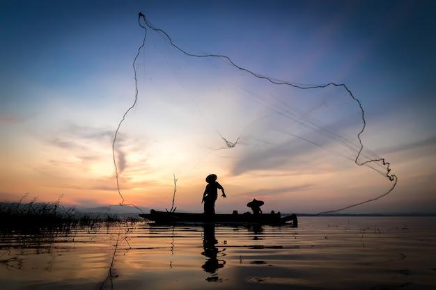 어부의 캐스팅은 나무 보트, 오래된 lanter와 함께 아침 일찍 물고기에 나갑니다