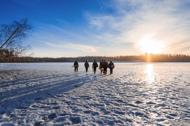 Fishermen go on the ice in winter on a sunny day