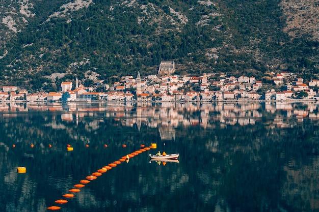 Рыбаки в лодке рыбачат в которской бухте вид на город