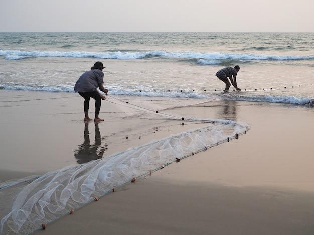 海から漁網を引っ張る漁師
