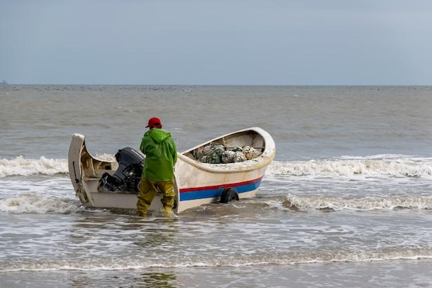 釣りに行く準備ができている漁師は彼らの漁船を海に押し込みました