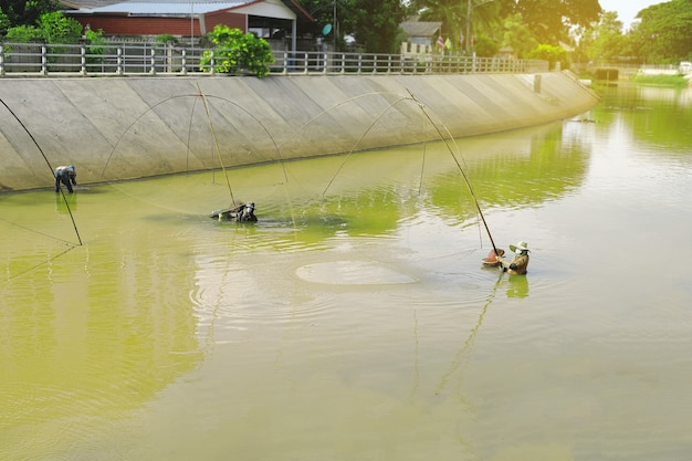 Fishermen using square nets called yo to catch fish,fishermen are catching fish with yo.thailand local catch fish. Premium Photo