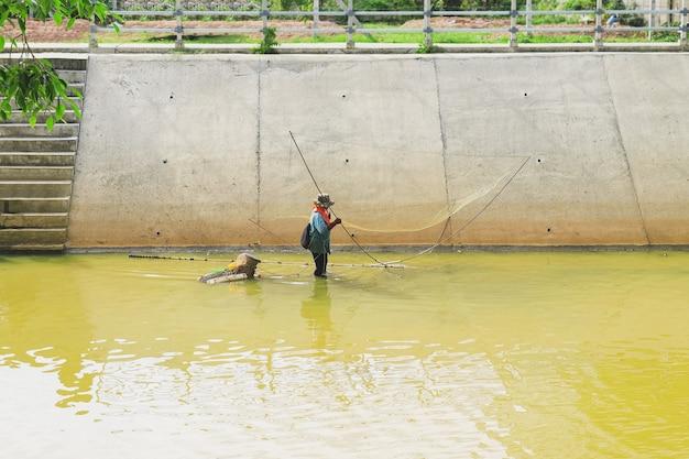 漁師はヨと呼ばれる四角い網を使って魚を捕まえ、漁師はヨで魚を捕まえています。タイの地元の魚を捕まえます。