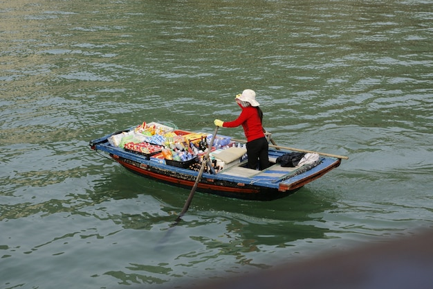 Fishermen and vendors in traditional vietnamese boats crossing the bay.