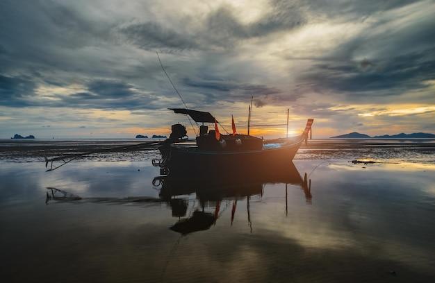 Деревянная лодка рыболовства с низким освещением закатного неба и темной тенью.