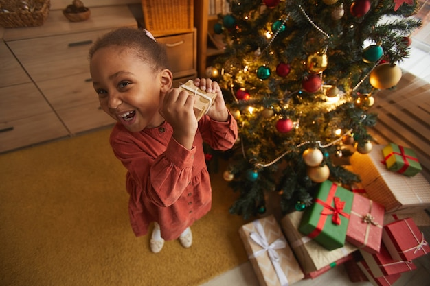 家で木のそばに立っている間、クリスマスプレゼントを開く興奮したアフリカ系アメリカ人の女の子の魚眼レンズの肖像画、コピースペース