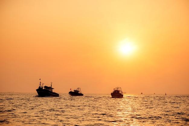 美しい黄金の夕日、ケララ州、インドの高知港に戻る海でのフィッシン産業ボート