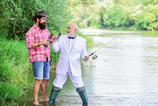 釣りとビールを飲む。自然の背景をリラックスする男性。楽しくリラックスしてください。週末の時間。ひげを生やした男とエレガントなビジネスマンが一緒に釣りをしています。釣りのスキル。フックラインとシンカーでロッドをセットアップします。